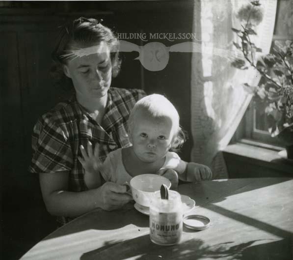 Adéle och barn dricker honungsvatten i köket, 1948