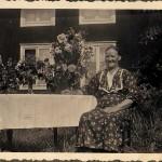Sally, Hildings mamma sitter framför gammelbyggningen i Ollas.