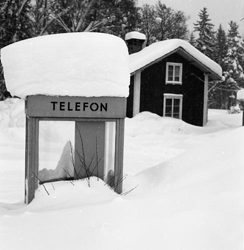 """M 66 194: """"Snövintern, februari 1982. Telefonkiosken och lillbyggningen vid Modigs diversehandel, Glösbo"""". Foto: Hilding Mickelsson"""