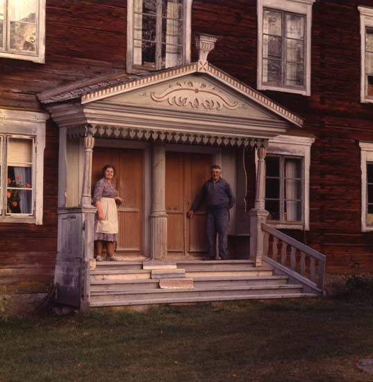 M 42 554: JON-LARS, Långhed, Alfta Stor och elegant förstukvist daterad 1857 med två ingångar till hushållen, och gårdens gamla bondepar Beda och Olle Johansson. Foto: Hilding Mickelsson