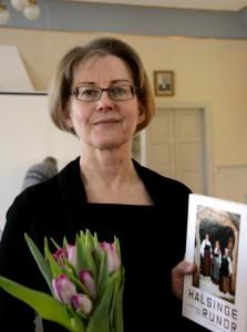 """Ingela Broström tackas för föreläsningen med blomster och """"Hälsinge Runor"""". Foto: Anna Hildingson Edling"""