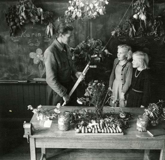 M 4458 Admins anteckning: Här visar Hilding Mickelsson skolbarnen hur de skall sköta om sina grönsaksodlingar på bästa sätt