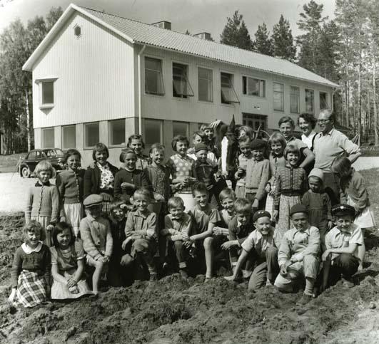"""M 827:31/5 1956 Jan Falkeborn Karin Paulsson (gift Persson) """"Annefors skola i maj 1956. Lärarna Karin Paulsson och Jan Falkeborn med skolbarnen som var med i en odlarklubb med bl.a. grönsaks- och potatisodling."""" Foto: Hilding Mickelsson"""