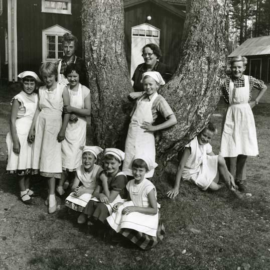 M 851:Unga Odlare i Annefors färdiga för konserveringskurs under hemkonsulent Maggie Banks ledning. I bakgrunden syns gamla skolan som senare blev bybornas samlingslokal. Tyvärr så brann skolan ner. Foto den 18 augusti 1956. Foto: Hilding Mickelsson
