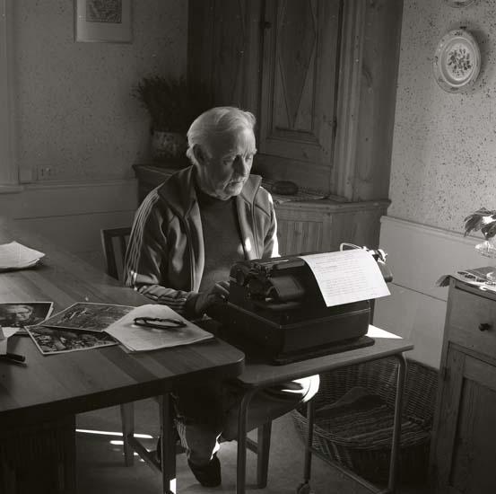 M 68 590: Helge Törnros skriver bildtext till Finnskogsboken 26/4 -84. Foto: Hilding Mickelsson