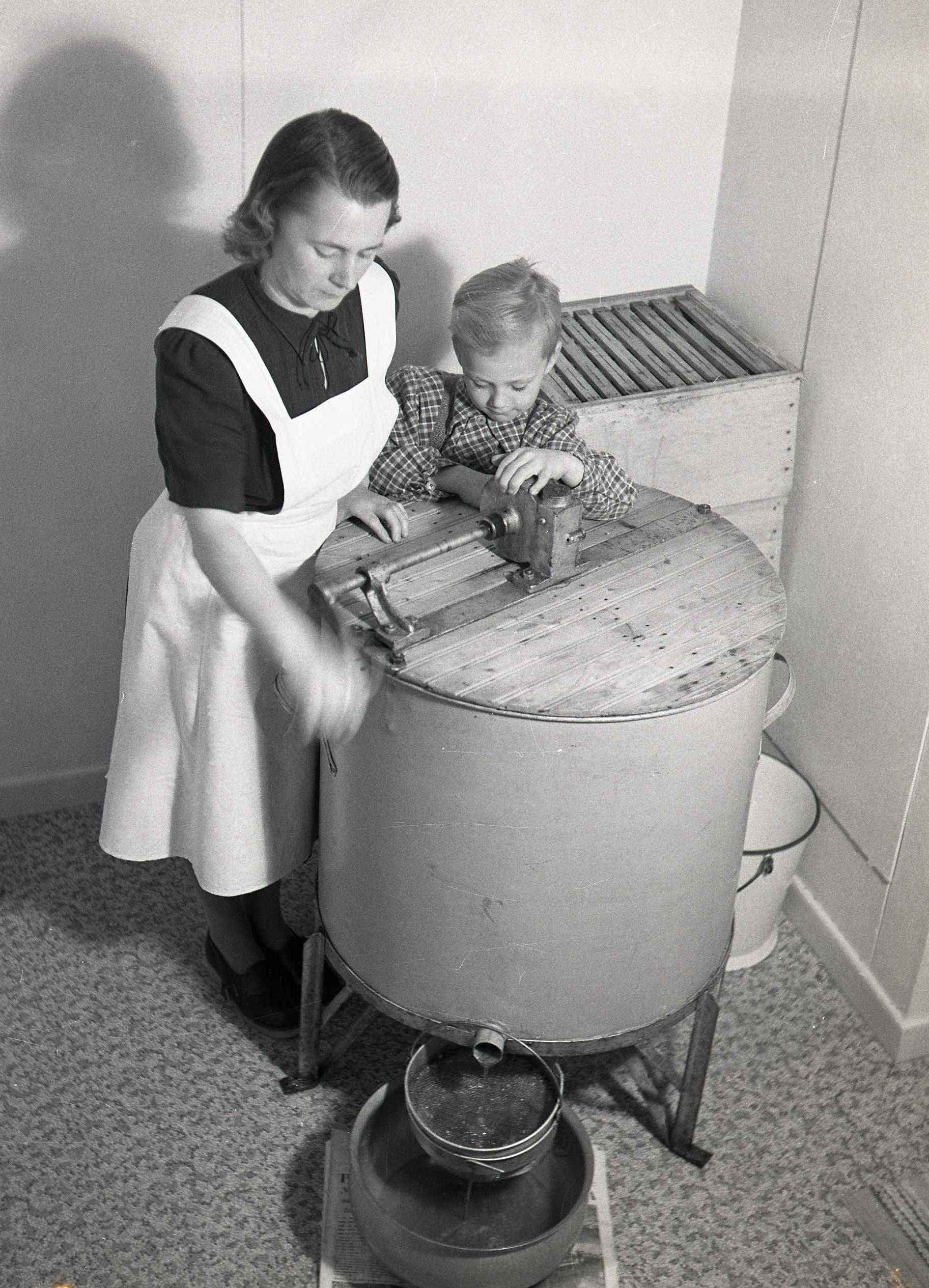 M 115 869: Adéle och en av pojkarna slungar honung, november 1951. Foto: Hilding Mickelsson©