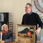 Sällskapets ordförande Göran Bratt visar här upp en av Hilding Mickelssons målade tavlor. Till vänster sekreteraren Lars-Holger Röstlund. Fotot:Anna Hildingson Edling
